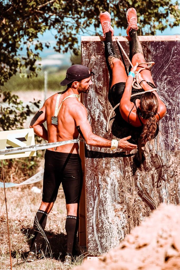 Course d'obstacle. un homme aide, motive une femme qui franchie un mur en obstacle