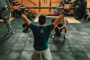 Un homme soulève une barre avec des poids. il est bras tendu